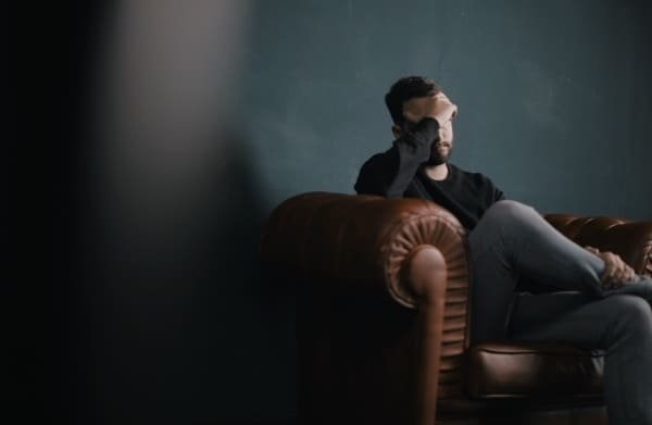 man sitting on lounge holding head