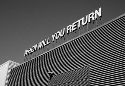 image of building with sign saying 'when will you return'